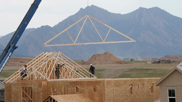 Workers install roof trusses onto a new house in Arvada, Colorado July 10, 2017. REUTERS/Rick Wilking - RTX3AX1O