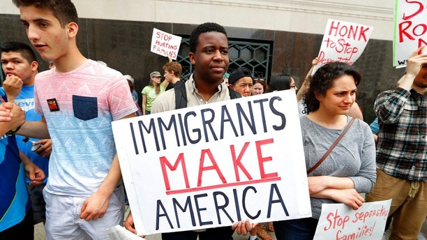 FILE - In this May 16, 2017, file photo, Torianto Johnson, a freshman at Pioneer High School in Ann Arbor, Mich., holds a sign supporting immigrants during a rally outside a federal courthouse in Detroit. For years, immigrants have checked in regularly with federal deportation agents to show they've been following the country's laws even though they have been ordered to leave. Now, in cases spanning from Michigan to California, many of those who have exhausted their legal options are being told their time here is up. (AP Photo/Paul Sancya, File)