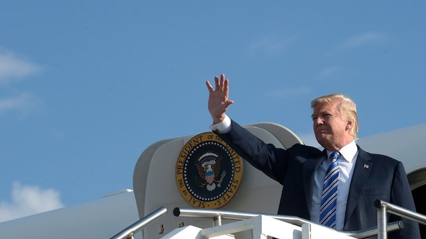 President Donald Trump waves as he walks down the steps of Air Force One at Tri-State Airport in Huntington, W.Va., Thursday, Aug. 3, 2017. Trump is in West Virginia for a campaign-style rally in Huntington, W.Va., where it is expected that West Virginia Gov. Jim Justice, a Democrat, will announce at the rally with Trump that he is changing parties. (AP Photo/Susan Walsh)