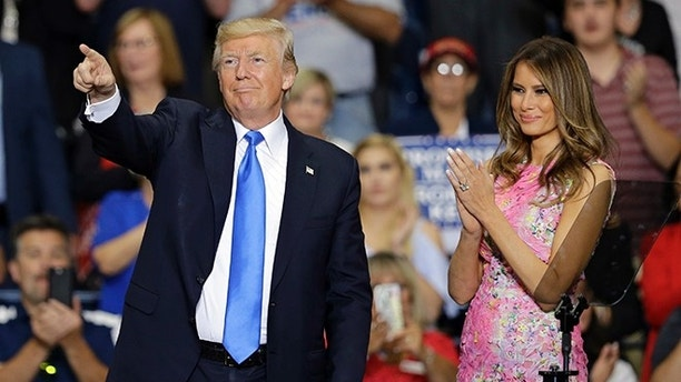 President Donald Trump points to his supporters as first lady Melania Trump watches after speaking at the Covelli Centre, Tuesday, July 25, 2017, in Youngstown, Ohio. (AP Photo/Tony Dejak)