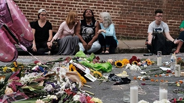 "Women sit by an impromptu memorial of flowers commemorating the victims at the scene of the car attack on a group of counter-protesters during the ""Unite the Right"" rally as people continue to react to the weekend violence in Charlottesville, Virginia, August 14, 2017. REUTERS/Justin Ide     TPX IMAGES OF THE DAY - RTS1BTBR"