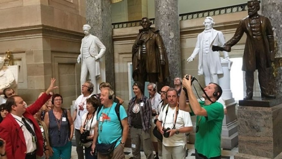 A tour guide talks to tourists inside the Capitol's Statuary Hall on Thursday near the statue of Jefferson Davis (center, in bronze).