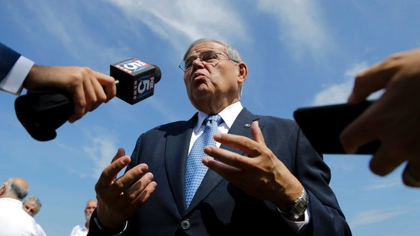 U.S. Sen. Bob Menendez, center, takes questions after a news conference talking about flood insurance, Thursday, Aug. 17, 2017, in Union Beach, N.J.