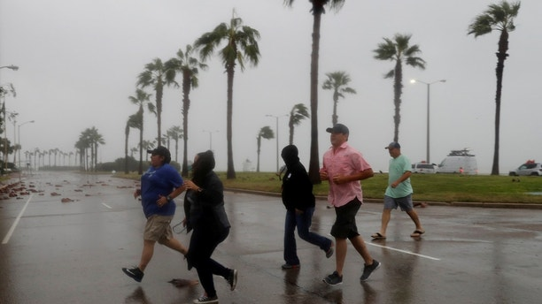 A group of people race across the street as winds from Hurricane Harvey escalated in Corpus Christi, Texas, U.S. August 25, 2017. REUTERS/Adrees Latif - RTX3DDRP