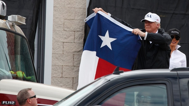 President Donald Trump holds up a Texas flag after speaking with supporters outside Firehouse 5 Tuesday, Aug. 29, 2017, following a briefing on Harvey relief efforts.  (AP Photo/Evan Vucci)