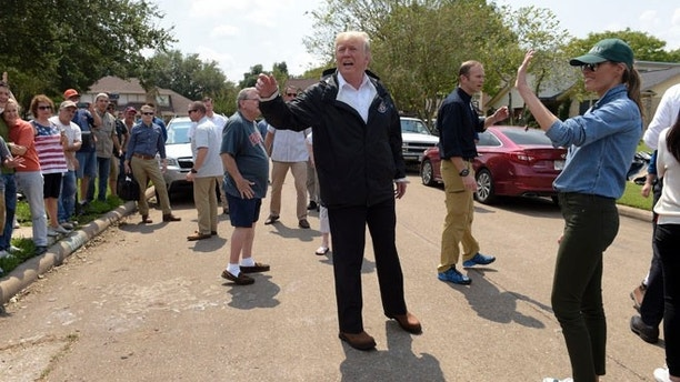 President Donald Trump and first lady Melania Trump stop to talk with residents impacted by Hurricane Harvey in a Houston neighborhood, Saturday, Sept. 2, 2017. (AP Photo/Susan Walsh)