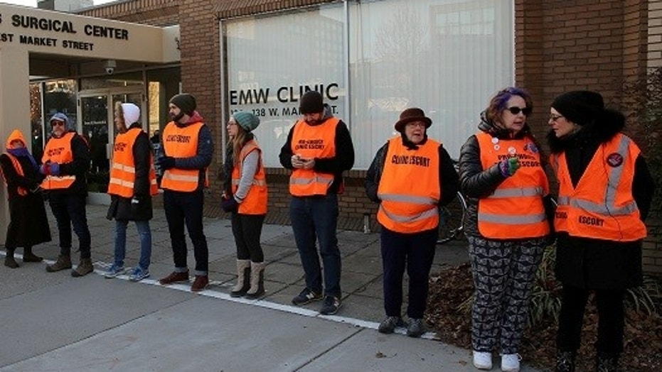Escorts stand outside of EMW Women's Surgical Center in Louisville, Ky., the last abortion clinic in the state. The center is embroiled in a legal battle with the state over requirements to stay open.