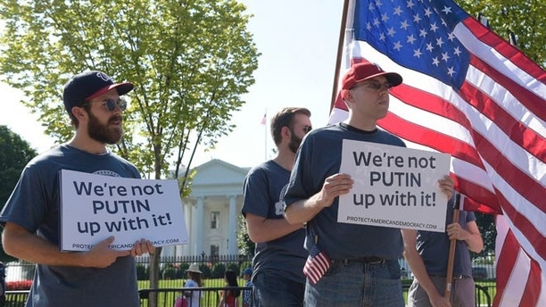 Protesters gather at the White House in Washington, Saturday, Sept. 16, 2017, during a rally encouraging President Donald Trump and House Speaker Paul Ryan to defend American democracy from Russian interference. (AP Photo/Susan Walsh)