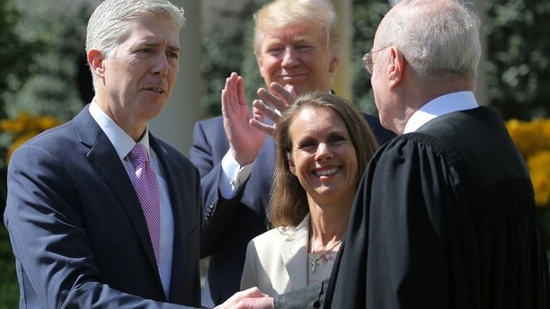 Judge Neil Gorsuch shakes hands with Supreme Court Associate Justice Anthony Kennedy after being sworn in as an Associate Justice of the Supreme Court, accompanied by Louise Gorsuch (C) and U.S. President Donald J. Trump in the Rose Garden of the White House in Washington, U.S., April 10, 2017. REUTERS/Carlos Barria - RTX34YQB