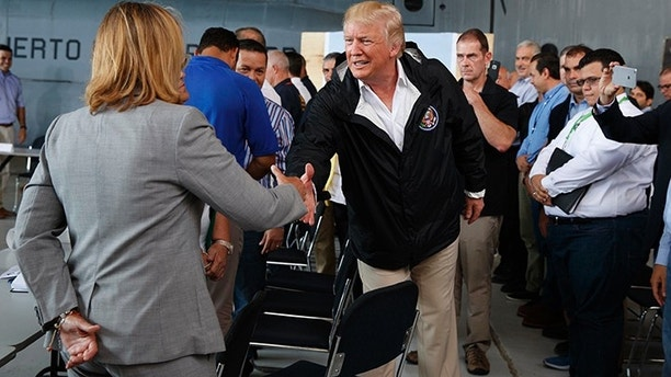 President Donald Trump shakes hands with San Juan Mayor Carmen Yulin Cruz during a briefing on hurricane recovery efforts with first responders at Luis Muniz Air National Guard Base, Tuesday, Oct. 3, 2017, in San Juan, Puerto Rico. (AP Photo/Evan Vucci)