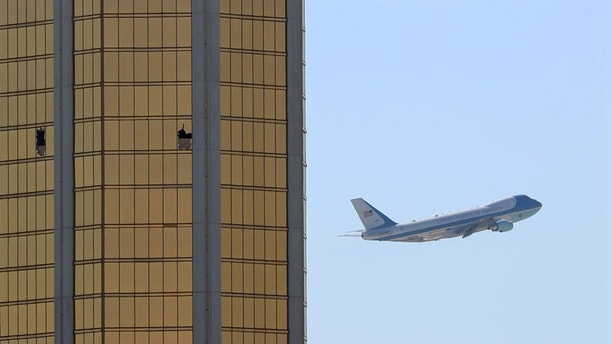 Air Force One departs Las Vegas past the broken windows on the Mandalay Bay hotel, where shooter Stephen Paddock conducted his mass shooting along the Las Vegas Strip in Las Vegas, Nevada, U.S., October 4, 2017.       REUTERS/Mike Blake - RC1585FEE8C0