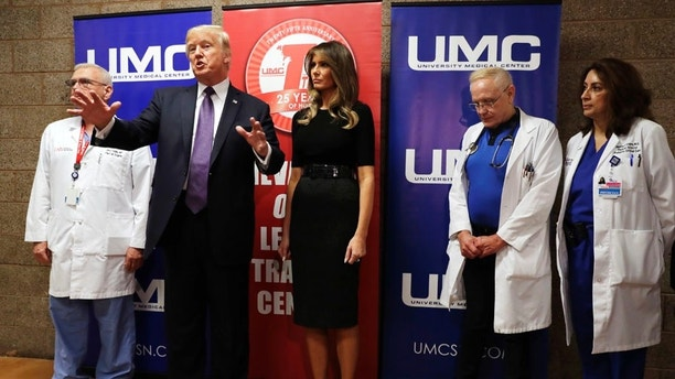 President Donald Trump talks as first lady Melania Trump and surgeon Dr. John Fildes, left, listens at the University Medical Center after Trump met with survivors of the mass shooting Wednesday, Oct. 4, 2017, in Las Vegas. (AP Photo/Evan Vucci)