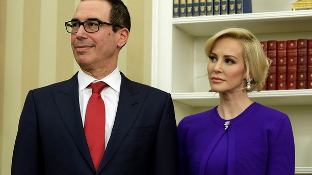 Steve Mnuchin stands with his fiancee Louise Linton before swearing in as Treasury Secretary in the Oval Office of the White House in Washington February 13, 2017.