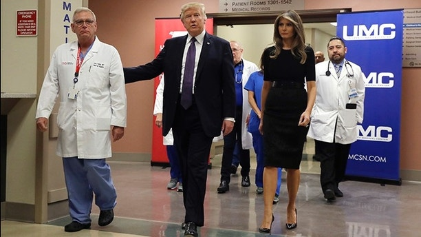 President Donald Trump and first lady Melania Trump walk with surgeon Dr. John Fildes at the University Medical Center after meeting with victims of the mass shooting Wednesday, Oct. 4, 2017, in Las Vegas. (AP Photo/Evan Vucci)