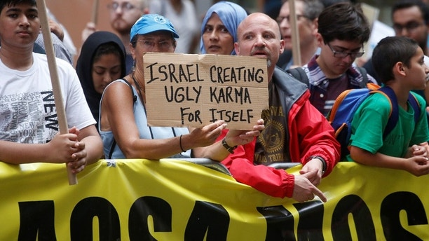 An anti Israel protester holds up a sign during a demonstration in Times Square in the Manhattan borough of New York City, New York, U.S. June 23, 2017.   REUTERS/Carlo Allegri - RC125AE1E000