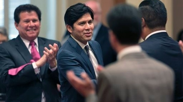 FILE - In this June 16, 2014 file photo Sen. Kevin de Leon,D-Los Angeles, second from left, receives congratulations from other lawmakers after he was elected the new Senate President Pro Tem at the Capitol in Sacramento, Calif.   De Leon will be sworn-in as the new Senate leader at a lavish evening event, with far more pomp than the typical Capitol affair that marks the change leadership, at the Walt Disney Concert Hall, in Los Angeles, Wednesday, Oct. 15, 2014.  De Leon succeeds Senate President Pro Tem Darrell Steinberg, D-Sacramento, who is leaving due to term limits. (AP Photo/Rich Pedroncelli, File)