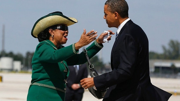 U.S. President Barack Obama is greeted by U.S. Rep. Frederica Wilson (D-FL) after arriving at Miami International Airport in Florida October 11, 2012.         REUTERS/Larry Downing  (UNITED STATES - Tags: POLITICS ELECTIONS) - GM1E8AC07E401
