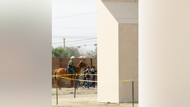 A group of people are detained by Border Patrol agents on horseback after crossing crossing the border illegally from Tijuana, Mexico, near prototypes for a border wall, right, are being constructed Thursday, Oct. 19, 2017, in San Diego. Companies are nearing an Oct. 26 deadline to finish building eight prototypes of President Donald Trump's proposed border wall with Mexico. (AP Photo/Gregory Bull)