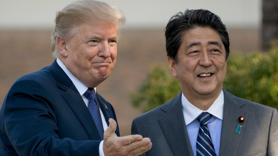 U.S. President Donald Trump and Japan's Prime Minister Shinzo Abe greet one another at Kasumigaseki Country Club outside Tokyo, Nov. 5, 2017.