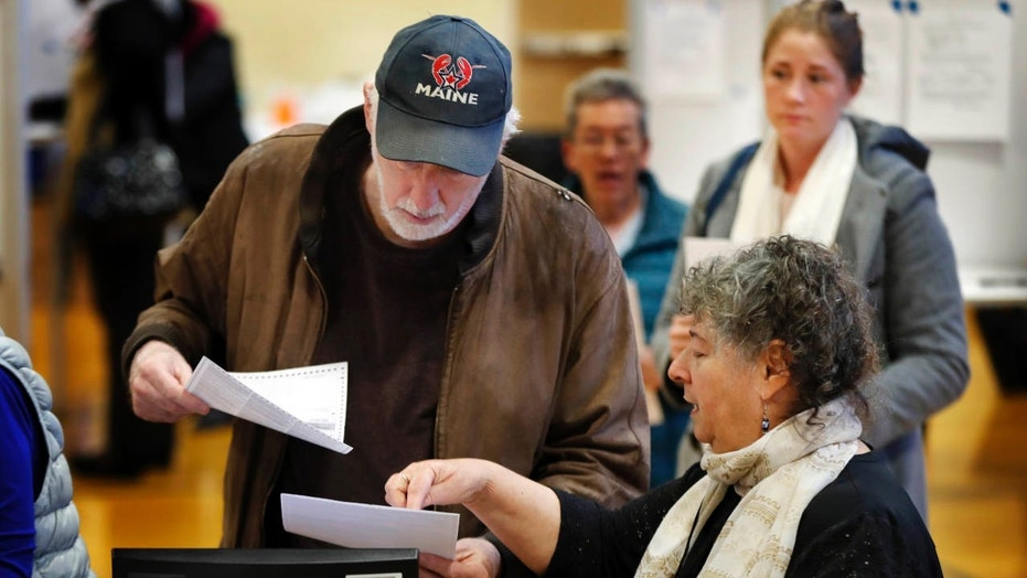 Michael Parent, left, gets instructions on submitting his ballots from warden Denise Shames while voting Tuesday, Nov. 7, 2017, in Portland, Maine.