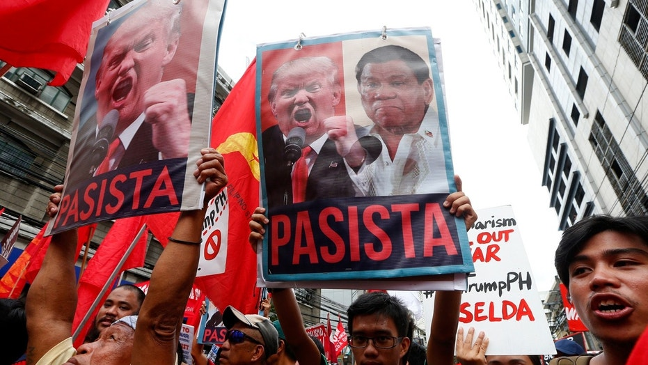 "Protesters shout slogans holding portraits of U.S. President Donald Trump and Philippines President Rodrigo Duterte during a rally near the U.S. Embassy in Manila, Nov. 10, 2017. The sign translates to ""Fascist."""