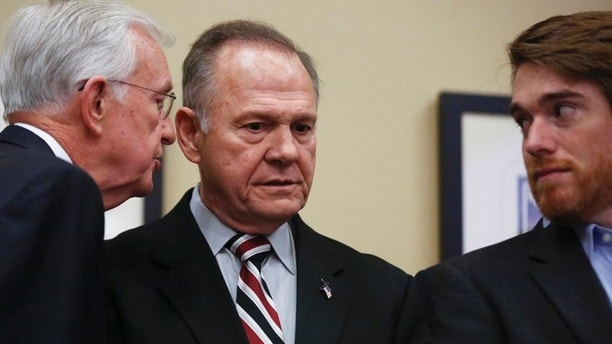 Former Alabama Chief Justice and U.S. Senate candidate Roy Moore listens as a campaign member talks to him before Moore speaks at the Vestavia Hills Public library, Saturday, Nov. 11, 2017, in Birmingham, Ala. According to a Washington Post story Nov. 9, an Alabama woman said Moore made inappropriate advances and had sexual contact with her when she was 14. (AP Photo/Brynn Anderson)