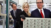 Treasury Secretary Steven Mnuchin, right, and his wife Louise Linton, hold up a sheet of new $1 bills, the first currency notes bearing his and U.S. Treasurer Jovita Carranza's signatures, Wednesday, Nov. 15, 2017, at the Bureau of Engraving and Printing (BEP) in Washington. The Mnuchin-Carranza notes, which are a new series of 2017, 50-subject $1 notes, will be sent to the Federal Reserve to issue into circulation. At left is BEP Director Leonard Olijar. (AP Photo/Jacquelyn Martin)