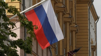 A Russian flag flies in front of the U.S. embassy building in Moscow, Russia, July 28, 2017. REUTERS/Tatyana Makeyeva - RTX3DADD