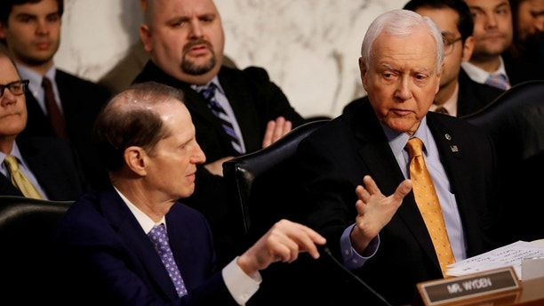 "Sen. Orrin Hatch (R-UT) speaks with Sen. Ron Wyden (D-OR) during a markup on the ""Tax Cuts and Jobs Act"" on Capitol Hill in Washington, U.S., November 15, 2017. REUTERS/Aaron P. Bernstein - RC1EBBBFC720"