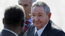 Flanked by a bodyguard, left, and a diplomatic protocol officer, Cuba's President Raul Castro makes his way to a waiting car after arriving at the Arturo Merino Benitez International Airport in Santiago, Chile, Friday, Jan. 25, 2013. Castro along with other Latin American, Caribbean and European leaders are gathering in Santiago for this weekend's CELAC-EU economic summit. (AP Photo/Luis Hidalgo)
