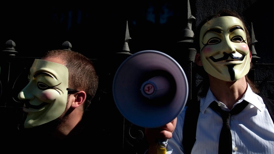 """May 15, 2011: People wearing masks often used by a group that calls itself """"Anonymous"""" take part in a rally in Madrid."""