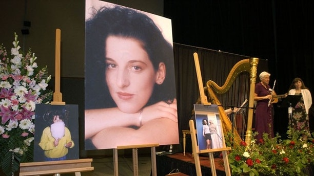 May 28, 2002: Photographs of Chandra Levy are displayed while the musicians stand guard at the Levy memorial service at the Modesto Center Plaza in Modesto, California. More than nine years after the inmate's disappearance from Washington, DC became a mystery that caught national attention, the homicide trial returns after a six-day hiatus.