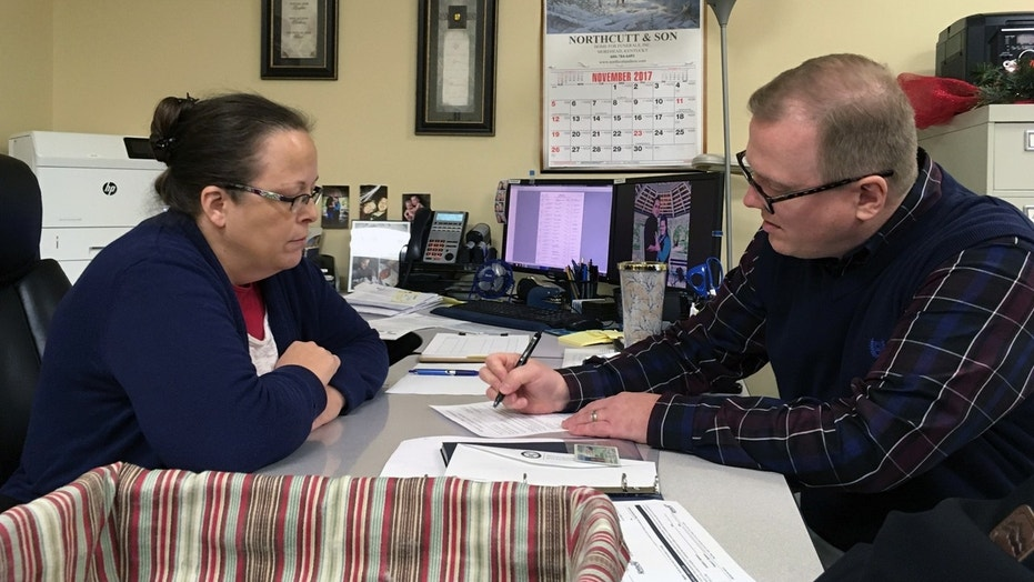 David Ermold, right, files to run for Rowan County Clerk in Kentucky as Clerk Kim Davis looks on Wednesday.
