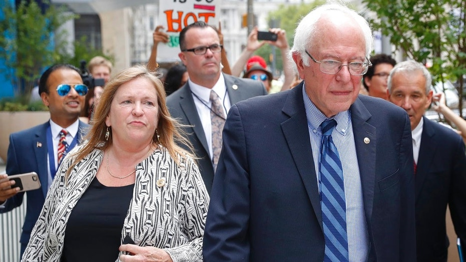 U.S. Sen. Bernie Sanders, I-Vt., and wife Jane Sanders walk in Philadelphia during the final day of the Democratic National Convention, July 28, 2016. Sanders remains under federal investigation for a land deal she made as president of Burlington College in Vermont in 2010.