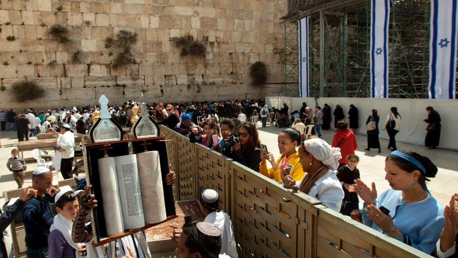 A man holds up a Torah scroll as women stand across a fence at the Western Wall, the holiest site where Jews can pray in Jerusalem's old city, Wednesday, April 10, 2013.