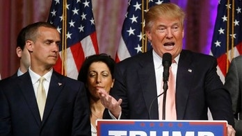 FILE - -In this March 15, 2016 file photo, Donald Trump's campaign manager Corey Lewandowski  listens at left are Trump speaks in Palm Beach, Fla. Florida police have charged Lewandowski with simple battery in connection with an incident earlier in the month involving a reporter. (AP Photo/Gerald Herbert, File)