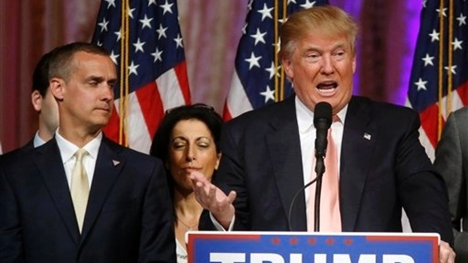 Corey Lewandowski, left, appears onstage as then-candidate Donald Trump speaks in Palm Beach, Fla., March 15, 2016.