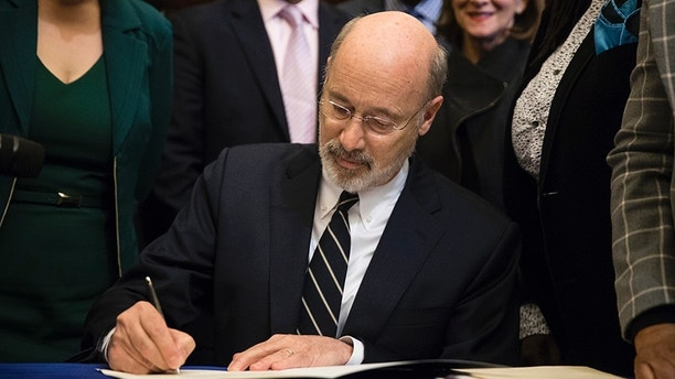 Pennsylvania Gov. Tom Wolf vetoes a bill passed by the Republican-controlled Legislature to limit abortions to the first 20 weeks of pregnancy at City Hall in Philadelphia, Monday, Dec. 18, 2017. (AP Photo/Matt Rourke)