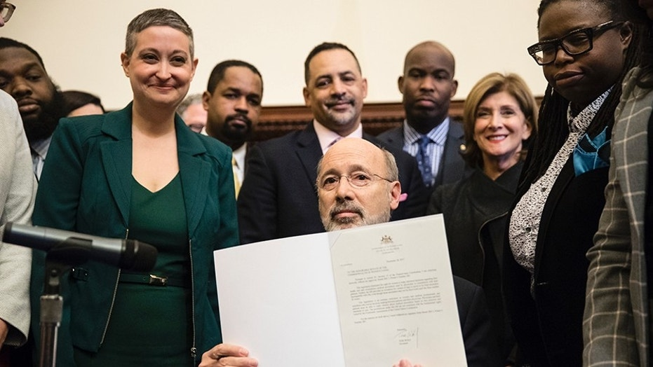 Pennsylvania Gov. Tom Wolf displays his signature after vetoing a bill passed by the Republican-controlled Legislature to limit abortions to the first 20 weeks of pregnancy at City Hall in Philadelphia, Monday, Dec. 18, 2017.
