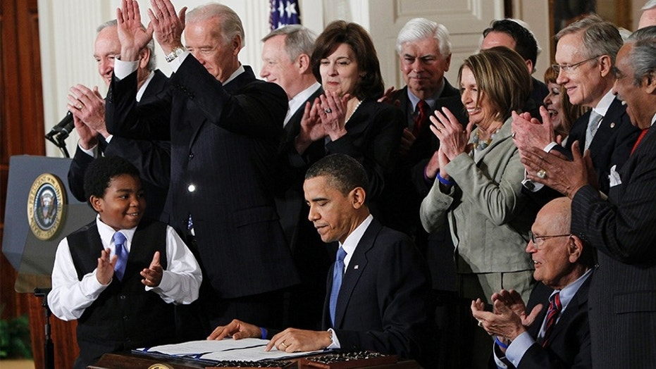 In this March 23, 2010, file photo President Barack Obama is applauded after signing the Affordable Care Act into law in the East Room of the White House in Washington.