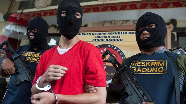Indonesian policemen hold rifles while guarding recaptured U.S. citizen and inmate Christian Beasley, who escaped from Kerobokan Prison, at Badung police station in Denpasar, Bali, Indonesia, December 20, 2017, in this photo taken by Antara Foto. Antara Foto/Nyoman Budhiana/via REUTERS   ATTENTION EDITORS - THIS IMAGE WAS PROVIDED BY A THIRD PARTY. MANDATORY CREDIT. INDONESIA OUT. - RC189728CEA0