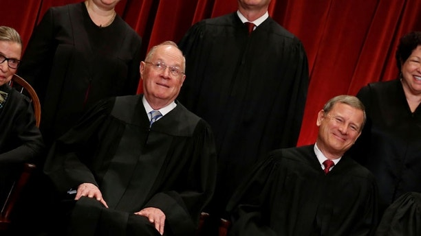 U.S. Supreme Court Justice Anthony Kennedy (L) reacts while chatting with Chief Justice John Roberts (R) during a new U.S. Supreme Court family photo including Justice Neil Gorsuch (not pictured), their most recent addition, at the Supreme Court building in Washington, U.S. June 1, 2017.  REUTERS/Jonathan Ernst - RC11BC0F6480