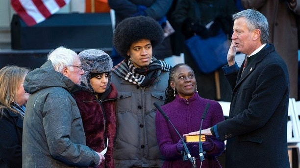 U.S. Sen. Bernie Sanders, I-Vt., left, swears in New York Mayor Bill de Blasio for a second term as mayor at City Hall in New York, Monday, Jan. 1, 2018. With De Blasio, second from left, are his daughter Chiara, son Dante, and wife, Chirlane McCray. (AP Photo/Craig Ruttle)