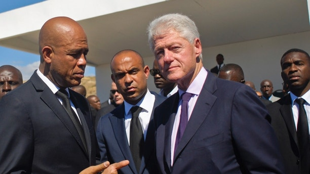 Haiti's President Michel Martelly, former U.S. President Bill Clinton and Haiti's Prime Minister Laurent Lamothe attend a memorial service remembering the lives lost in the January 2010 earthquake at the mass burial site at Morne