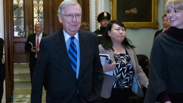 \Senate Majority Leader Mitch McConnell, R-Ky., answers to reporters as he walks to his office after speaking on the Senate floor at Capitol, Sunday, Jan. 21, 2018, in Washington. (AP Photo/Jose Luis Magana)\