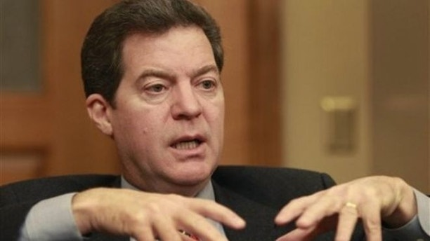 Dec. 21, 2010: Kansas Gov. Sam Brownback is shown before taking office talking with a reporter in Topeka.