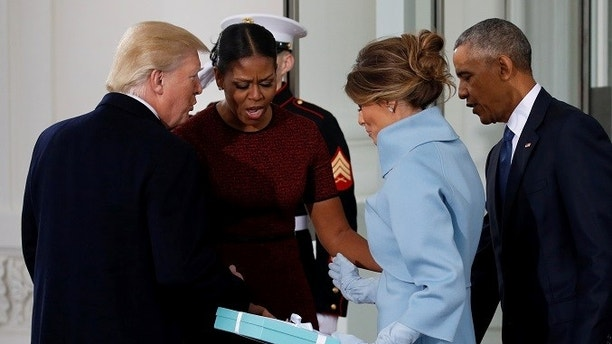 U.S. President-elect Donald Trump (L) and his wife Melania (3rd L) present a gift to U.S. first lady Michelle Obama and President Barack Obama as the Trumps arrive for tea before the inauguration at the White House in Washington, U.S. January 20, 2017. REUTERS/Jonathan Ernst - RC185816B880