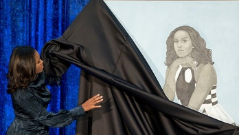 Former first lady Michelle Obama and Artist Amy Sherald, right, unveil Michelle Obama's official portrait at the Smithsonian's National Portrait Gallery, Monday, Feb. 12, 2018, in Washington. (AP Photo/Andrew Harnik)