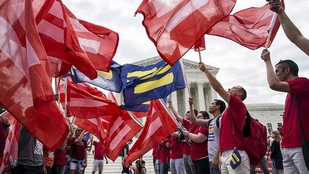 Supporters of gay marriage rally in front of the Supreme Court in Washington June 25, 2015. A decision in Obergefell v. Hodges, a test of a constitutional right to same-sex marriage, is expected in the coming days.  REUTERS/Joshua Roberts - GF10000139019
