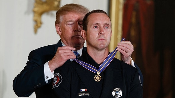 President Donald Trump presents the Public Safety Medal of Valor to Engineer Stephen Gunn of the Peoria, Ariz., Fire-Medical Department during an awards ceremony in the East Room of the White House, Tuesday, Feb. 20, 2018, in Washington. (AP Photo/Evan Vucci)